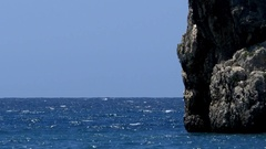 Blue water ocean that strikes a barren rock that rises from the depths Stock Footage