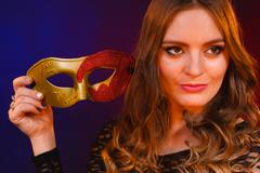 Closeup woman face with carnival mask on dark Stock Photos