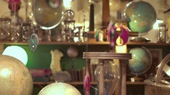 Young woman in antique shop plays with a globe Stock Footage