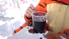 Young beautiful girl in costume tigers, drinking hot mulled wine from a plastic Stock Footage