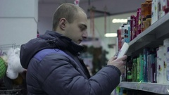 Man chooses shampoo in store Stock Footage