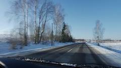 Winter landscape with the road the forest and the blue sky, car point of view Stock Footage
