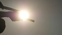 Manual fast knife sharpening silhouette against sun closeup Stock Footage