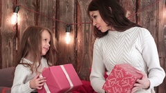 Mother and a cute little girl holding Xmas presents and trying to guess what's Stock Footage