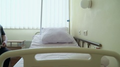 Adjustable hospital bed in a patient room. Using remote control Stock Footage