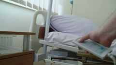 Using remote control to adjust the level of hospital bed in a patient room Stock Footage