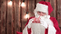 Santa Claus shaking a small gift tryring to guess what's inside Stock Footage