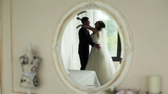 Happy newly wedded couple embrace and kiss feeling happy reflected in mirror Stock Footage