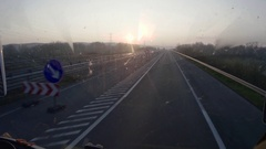 Car running on a highway in the early hours of the morning hours havin Stock Footage