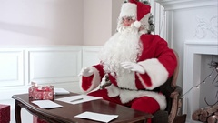 Busy Santa answering chidlren's letters while Santa's little helpers bringing Stock Footage