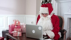 Modern Santa Claus working on his laptop and preparing presents Stock Footage