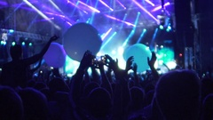 Happy crowd playing with huge balloons at concert, applauding to popular band Stock Footage