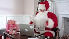 Busy Santa Claus preparing presents using laptop and digital tablet, sorting his Stock Footage