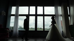 Confident groom meets happy bride first time seeing in wedding dress silhouetted Stock Footage