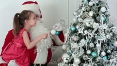 Fake Santa Claus decorating a Christmas tree holding a little girl in his arm Stock Footage