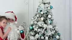 Santa Claus with pretty little girl decorating Christmas tree Stock Footage