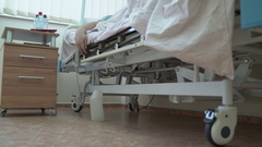 Man using remote control to adjust hospital bed in a patient room Stock Footage