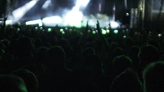 Silhouettes of people watching performance by singer, bright lights on stage Stock Footage