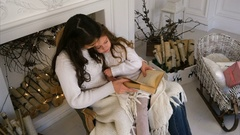 Happy mother and her beautiful daughter in white sweaters reading a book on Stock Footage