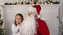 Undecided little girl on Santa Claus lap thinking about her present Stock Footage