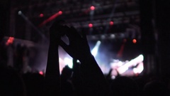People waving hands in air, enjoying good music and light show at concert hall Stock Footage
