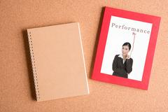 Note book and  photo of business woman in frame on wooden table Stock Photos