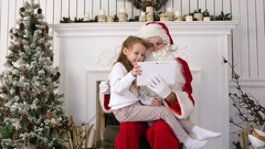 Happy little girl showing surprised Santa presents on tablet Stock Footage