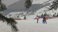 Children learn to ski school are seen through the branches of a tree Stock Footage