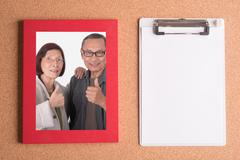 Clipboard and frame with picture of senior couples on wooden table Stock Photos
