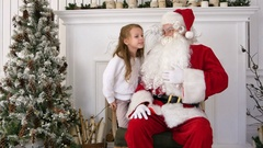 Smiling and shy girl sharing her Christmas dreams with Santa Stock Footage