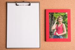 Clipboard and photo of woman in  frame on wooden table Stock Photos