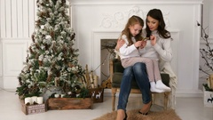 Mother showing her little daughter how to type a message to Santa on the phone Stock Footage