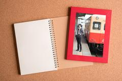 Note book and picture of woman in frame on wooden table Stock Photos