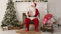 Happy Santa Claus reading Xmas messages on the phone and smiling while sitting Stock Footage