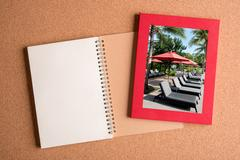 Note book and picture of pool bench and umbrella in frame on wooden table Stock Photos