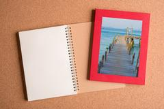 Note book and picture of old ship dock in frame on wooden table Stock Photos