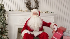 Good old Santa Claus sitting in a chair by the fireplace describing what Stock Footage