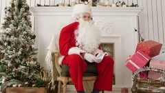 Laughing Santa sitting in a chair in his Christmas workshop Stock Footage