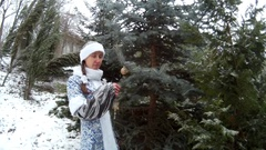 Snow Maiden in forest hanging toys on a firm tree smiling Ukraine Stock Footage