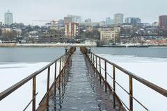 Frozen old pier at river side in winter time. Stock Photos