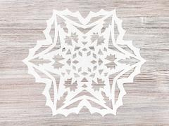 Snowflake carved from paper on light brown plank Stock Photos