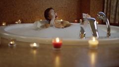 Sensual girl taking photo in bath in romantic atmosphere Stock Footage
