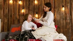 Young mother in white sweater plaiting her daughter hair Stock Footage