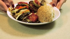The cooked ratatouille and a bun with sesame on a white plate. HD Stock Footage