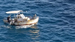 Boat fisherman moves up the sea with small waves and foamy blue Stock Footage