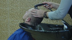 Man wash a head in the barber shop Stock Footage
