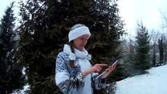 Snow Maiden in forest with tablet computer in front of firm pine tree smiling Stock Footage