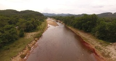 Red river flowing in the jungle overlooking the forest and mountains Stock Footage