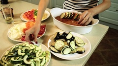 Cooking ratatouille. Female hands laying out a chopped vegetables in a dish. HD Stock Footage