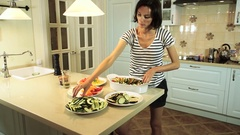 Young woman spreading out the chopped vegetables in a baking dish. HD Stock Footage